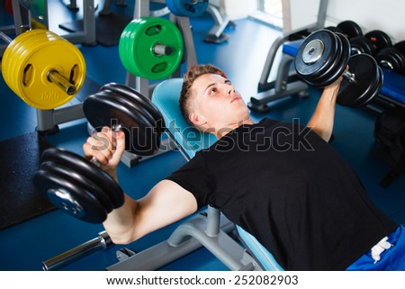 Exercising with dumbbells at gym. - stock photo