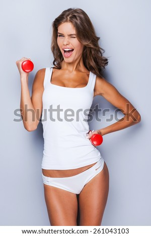 Exercising with fun. Attractive young sporty woman in tank top and panties exercising with dumbbells and smiling while standing against grey background   - stock photo