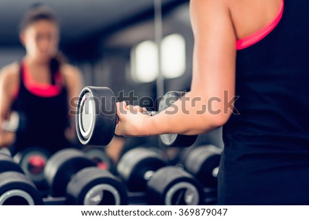 Exercising with weights, looking at mirror. Focus on hand - stock photo