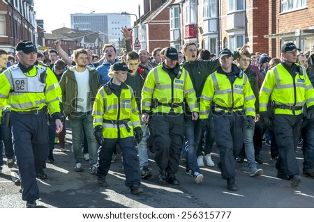 EXETER, ENGLAND - FEBRUARY 21, 2015: Devon and Cornwall Police escort Plymouth Argyle FC football fans at the League 2 football match between Exeter City FC and Plymouth Argyle FC  - stock photo