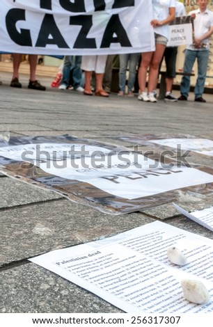 EXETER, ENGLAND - JULY 15, 2014: List of the Palestinians who have been killed by the Israeli army, with a Gaza banner in the background during the Peace Vigil for Gaza in Exeter's Princesshay Square. - stock photo