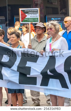 EXETER, ENGLAND - JULY 15, 2014: Peace campaigners holding signs during the Peace Vigil for Gaza in Exeter's Princesshay Square to remember the dead in the Israeli invation of Gaza - stock photo