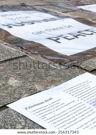 EXETER, ENGLAND - JULY 15, 2014: Peace signs, flowers and lists of Palestinians who have been killed by the Israeli army during the Peace Vigil for Gaza in Exeter's Princesshay Square. - stock photo