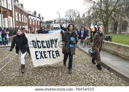 EXETER - FEBRUARY 11: Occupy Exeter activist march out of the Cathedral grounds during the Occupy Exeter leaving the Exeter Cathedral Green event in Exeter  on February 11, 2012 in Exeter, UK - stock photo