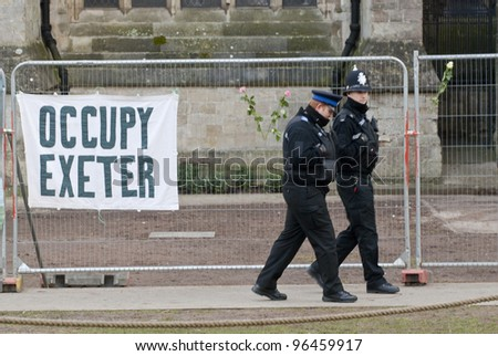 EXETER - FEBRUARY 11: Policemen walk past a banner tied to the  temporary fencing surrounding the area that was used by Exeter Occupy activists to have their camp on February 11, 2012 in Exeter, UK - stock photo