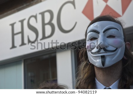 EXETER - JANUARY 28: Occupy Exeter activist wearing a Guy Fawkes mask campaigning outside the Exeter branch of HSBC bank  on January 28, 2012 in Exeter, UK - stock photo