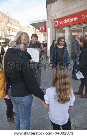 EXETER - JANUARY 28: Occupy Exeter activists campaign directly with the public outside the Exeter branch of Vodafone on January 28, 2012 in Exeter, UK - stock photo