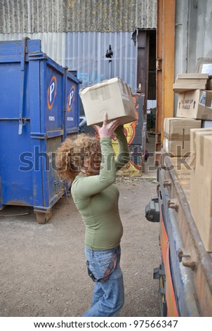EXETER - MARCH 9: Volunteer from BookCycle loads the last box of books into the container that is taking donated book to Ghana on March 9,  2012 in Exeter. - stock photo