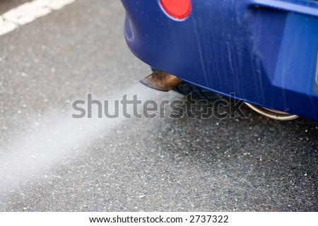 Exhaust pipe of a blue car - blowing out the pollution. - stock photo