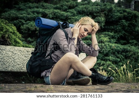 Exhausted and desperated young female backpacker - stock photo