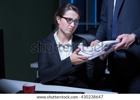 Exhausted and overworked office worker doing paperwork, working at night - stock photo