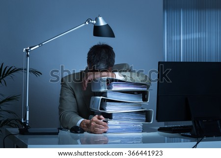 Exhausted businessman leaning head on binders while working late in office - stock photo