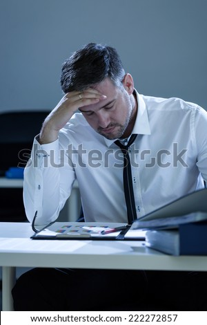 Exhausted businessman working overtime in the office - stock photo