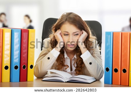 Exhausted businesswoman with binders by a desk. - stock photo