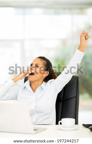 exhausted businesswoman yawning in office - stock photo