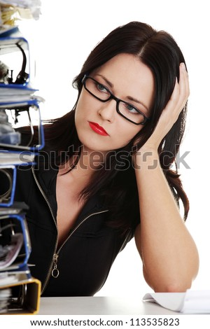 Exhausted female filling out tax forms while sitting at her desk. - stock photo