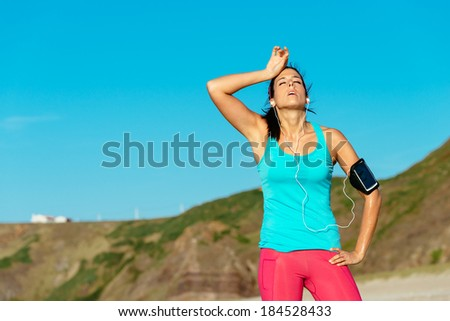 Exhausted female runner overtraining and sweating after training on hot summer at beach. Fitness sweaty woman on workout. - stock photo