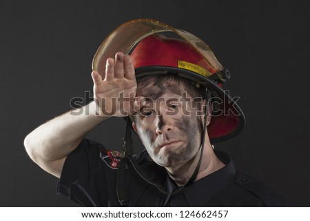Exhausted Fireman wiping his dirty forehead using his hand - stock photo