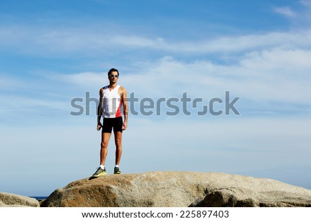 Exhausted fit runner after workout resting on seaside, successful winner standing on big hill, athlete standing on sea rocks at sunny summer day while resting after intensive training outdoors - stock photo