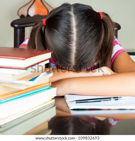 Exhausted girl sleeping on her desk after studying too much (there are books on the desk) - stock photo