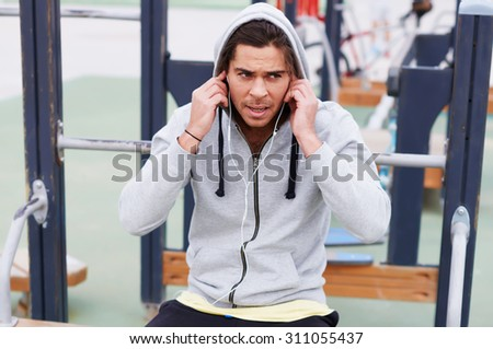 Exhausted handsome sportsman taking break after physical exercise outdoors while listening to music with headphones,tired young runner enjoying rest after hard workout outdoors on the horizontal bar  - stock photo