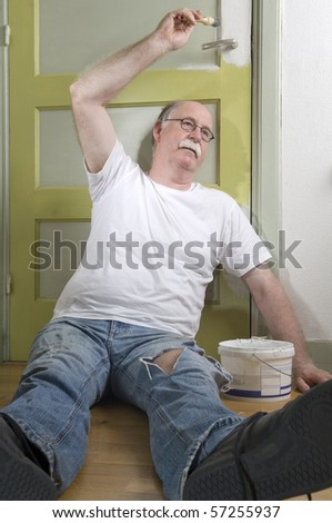 Exhausted house painter takes a break - stock photo