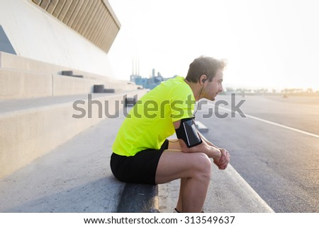 Exhausted male runner in fluorescent t- shirt taking break after workout training in sunrise time outdoors,young sports build man listening to music in headphones while resting after early morning run - stock photo