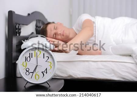 Exhausted man being awakened by an alarm clock in his bedroom - stock photo