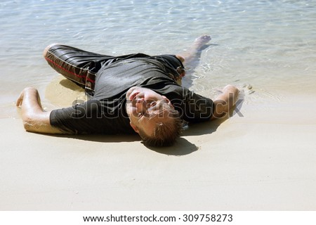 exhausted man crawled out of the sea and lying on the beach. Almost drowned person at the seashore. Survive the shipwreck in the sea. Drowned man lying on the sea beach. Exhausted swimmer survived. - stock photo