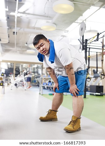 exhausted overweight young man in fitness center. - stock photo