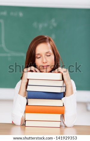 Exhausted student sleeping on her books with her chin resting on top of a tall stack of textbooks as she sits in the classroom - stock photo