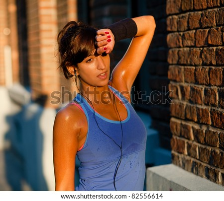 Exhausted sweaty young woman after a long run. Lit by the sunset light. - stock photo