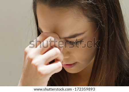 exhausted woman with headache, migraine, stress, hangover, mental problem under day time strong sunlight condition, hand holding forehead between eyebrow - stock photo