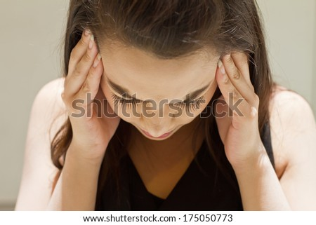 exhausted woman with headache, migraine, stress, hangover, mental problem under day time strong sunlight condition - stock photo