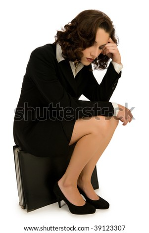 Exhausted young business woman sitting on large briefcase - stock photo