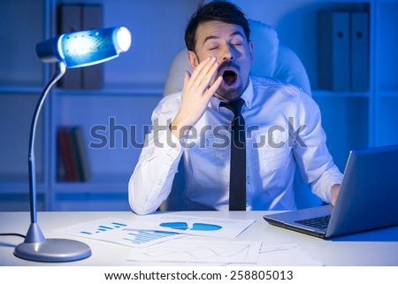 Exhausted young businessman is yawning at work in office. - stock photo
