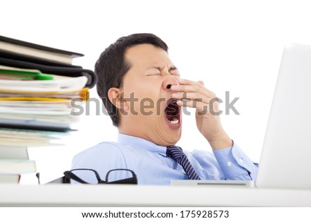 Exhausted young businessman yawning at work - stock photo