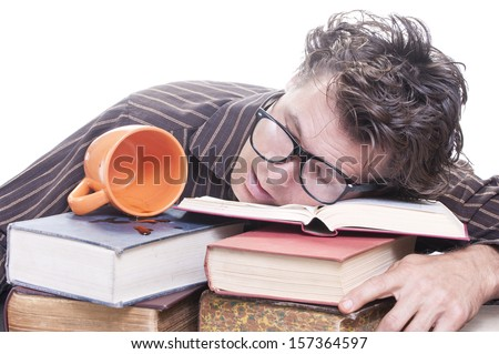 Exhausted young male Caucasian student with glasses asleep on pile of books next to spilled cup of coffee on white background with copy text space - stock photo