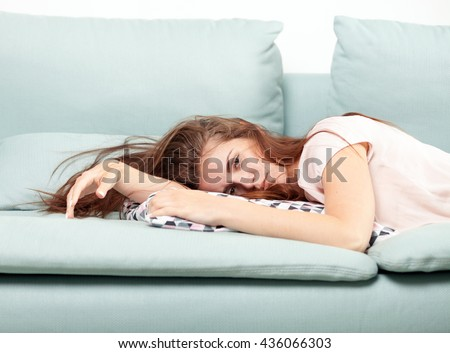 Exhausted young woman lying on couch at home, casual style indoor shoot - stock photo