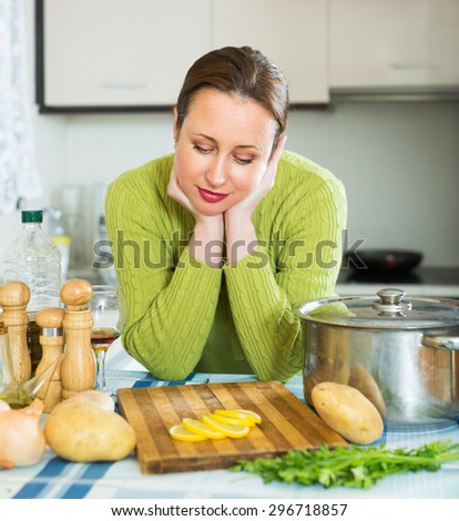 Exhausted young woman needs to make dinner after working day - stock photo