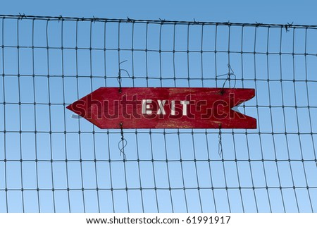 exit arrow sign on an old fence - stock photo