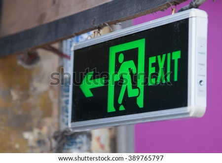 Exit sign points the way out in case of emergency - stock photo