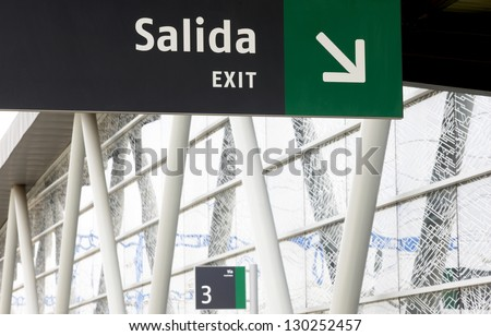 Exit signal at railway station with out of focus building - stock photo