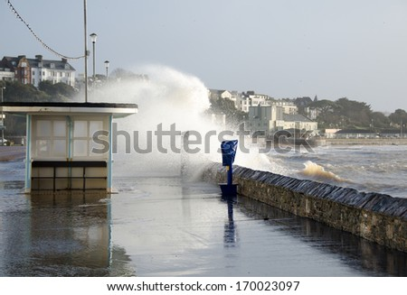 EXMOUTH, DEVON, ENGLAND - JAN 6, 2014:  Waves breaking over the sea wall at Exmouth.  There is limited flooding to the Esplanade but no property damage. - stock photo