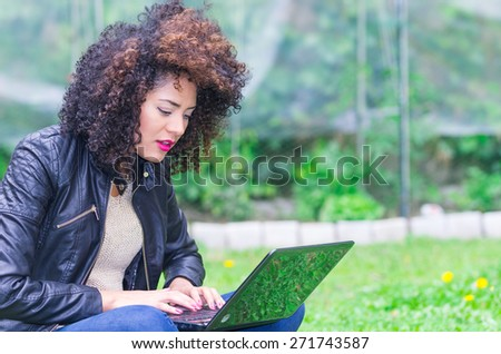 exotic beautiful young girl with dark curly hair using laptop typing in the garden - stock photo