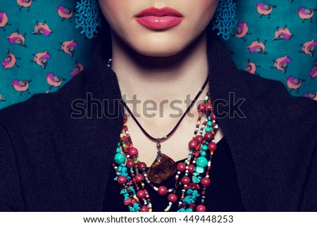 Exotic beauty concept. Beautiful young woman with bright make-up looking like well known Mexican artist posing over vintage background. Luxurious accessories. Retro style. Close up. Studio shot - stock photo