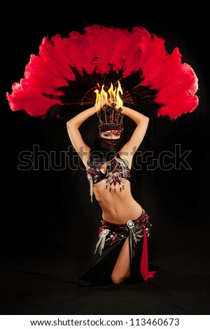Exotic belly dancer wearing a red and black costume with hijab and fire headdress. She is kneeling and holding a feather fan above her head. Shot in the studio on an isolated black background. - stock photo