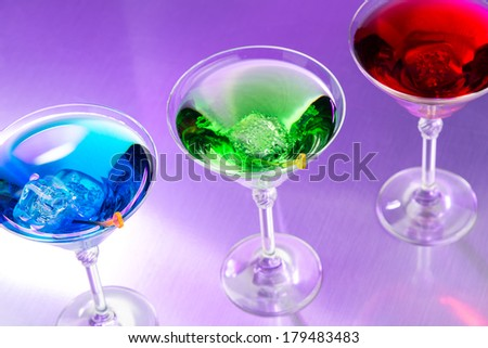 Exotic cocktails in purple light - stock photo