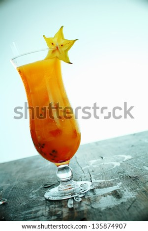 Exotic colourful orange carambola cocktail with fruit and ice served in a long glass on an old wooden bar counter with spillage around the foot of the glass, tilted angle with copyspace - stock photo