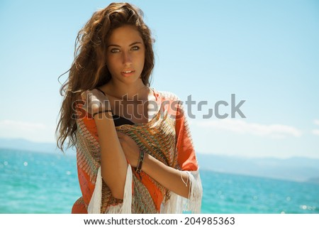 EXOTIC Fashionable young woman posing in bikini on a summer day . Shot on the beach. Toned in warm colors.Copy space for text. horizontal, outdoors. - stock photo